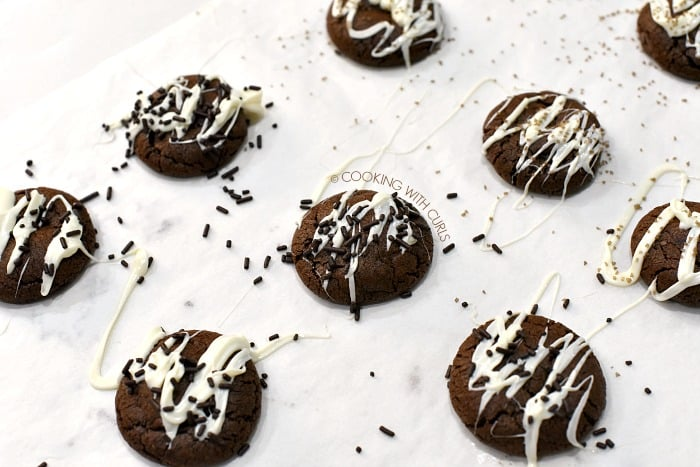 Baked cookies on parchment paper drizzled with melted chocolate and topped with sprinkles cookingwithcurls.com