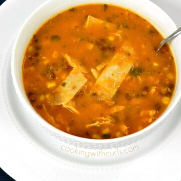 Chicken Tortilla Soup with beans, corn, tomatoes, chicken and cilantro served in a white bowl sitting on a large white plate