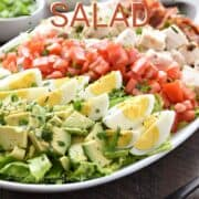 Chopped avocado, hard-boiled eggs, tomatoes, chicken, and bacon on a bed of lettuce with green onions, parsley, and ranch dressing in the background and title graphic across the top