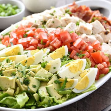 Chopped avocado, tomatoes, chicken, bacon, and sliced hard-boiled eggs on lettuce leaves.