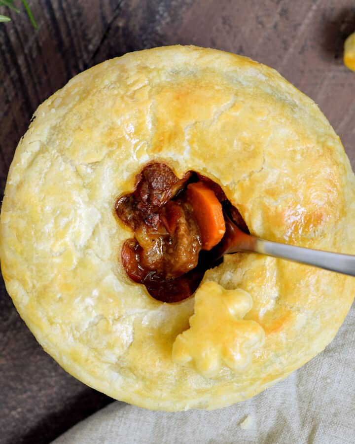 Looking down on a puff pastry topped steak pie with a fork sticking out of the center.