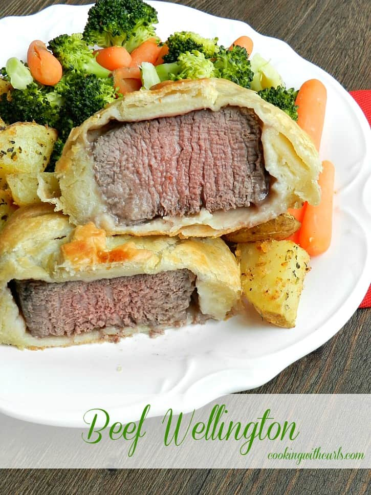 beef tenderloin wrapped in puff pastry served on a white plate with roast potatoes, broccoli and carrots