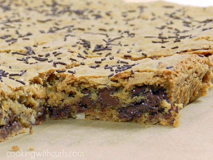 A pan of Blonde Brownies with the corner cut out laying on parchment paper.