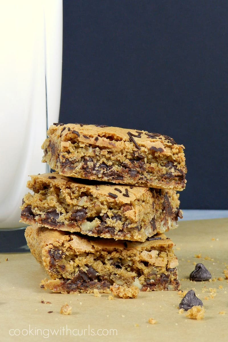 A stack of three Blonde Brownies, or Blondies, on parchment paper next to a glass of milk.