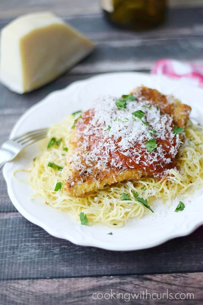 Chicken Parmesan served on a bed of of pasta   cookingwithcurls.com