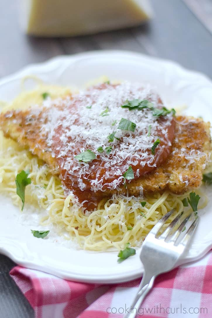 Chicken Parmesan served on a bed of pasta for a quick weeknight meal | cookingwithcurls.com