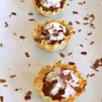 Four chocolate peanut butter pie bites lined up on a white platter sprinkled with shaved chocolate.