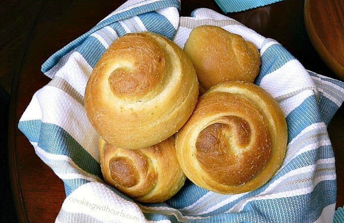garlic dinner rolls in a basket lined with a blue and white striped napkin