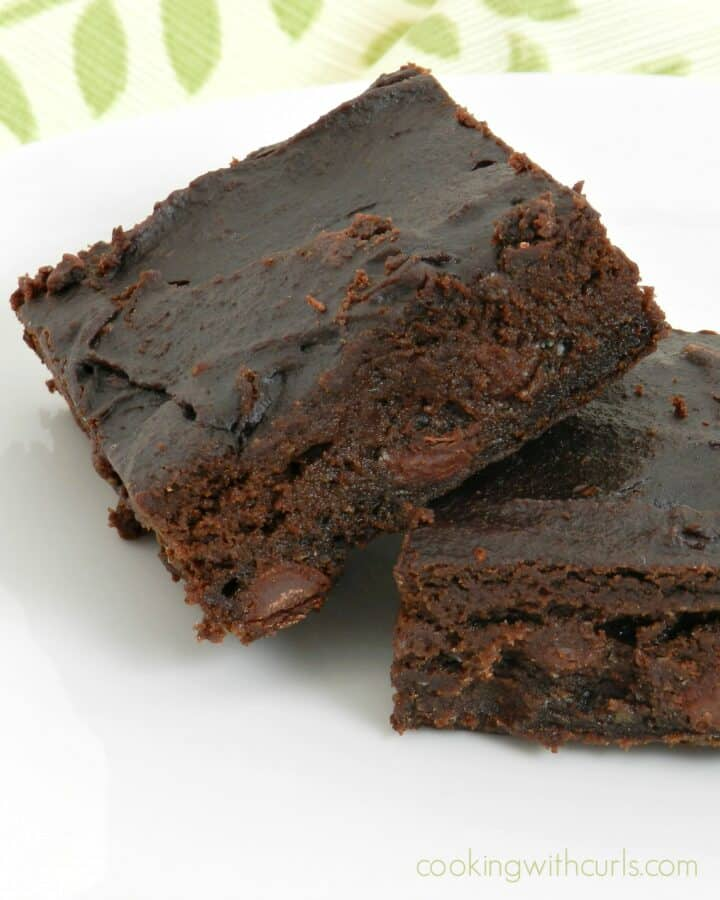 two dark fudgy avocado brownies leaning against each other on a white plate.