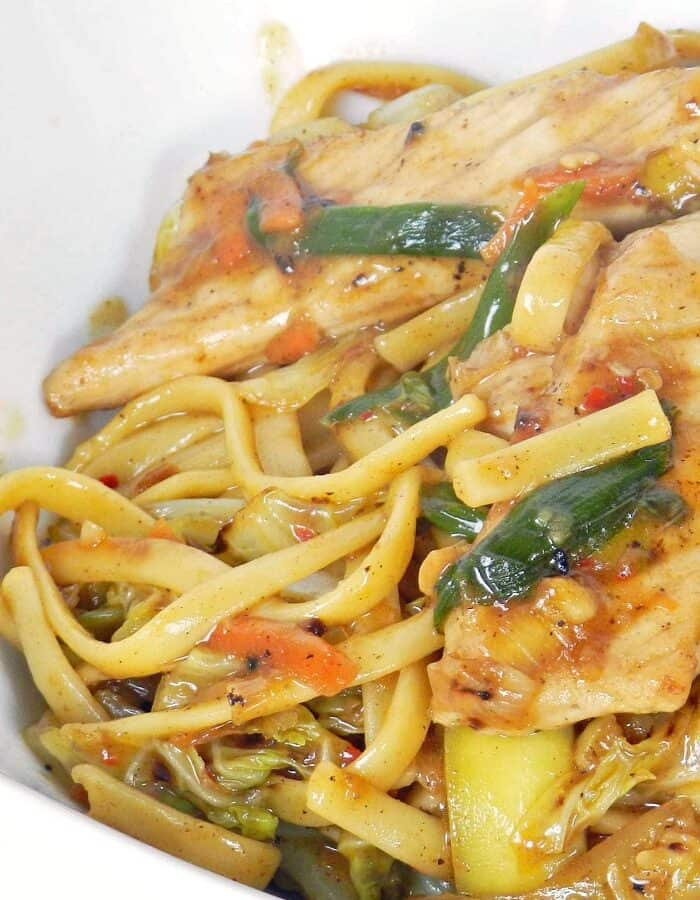 close up image of pork lo mein in a white bowl