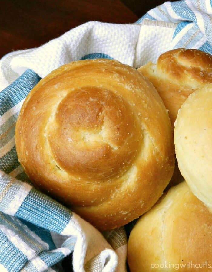 garlic dinner rolls pilled high in a blue striped napkin lined basket