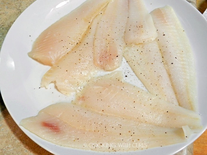Sole seasoned with salt and pepper on a large white plate
