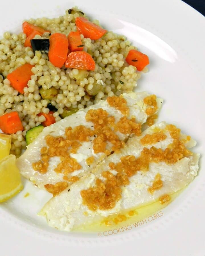 Sole topped with Caramelized Garlic on a white plate with couscous