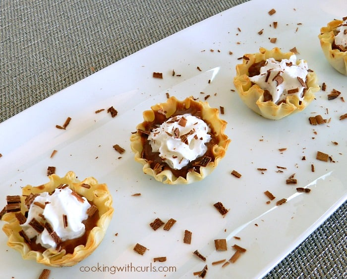 Three and a half Chocolate Peanut Butter Pie Bites lined up on a white platter.