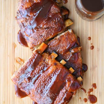 A slab of Guinness Barbecue Ribs on a wood cutting board with a jar of barbecue sauce in the upper right corner