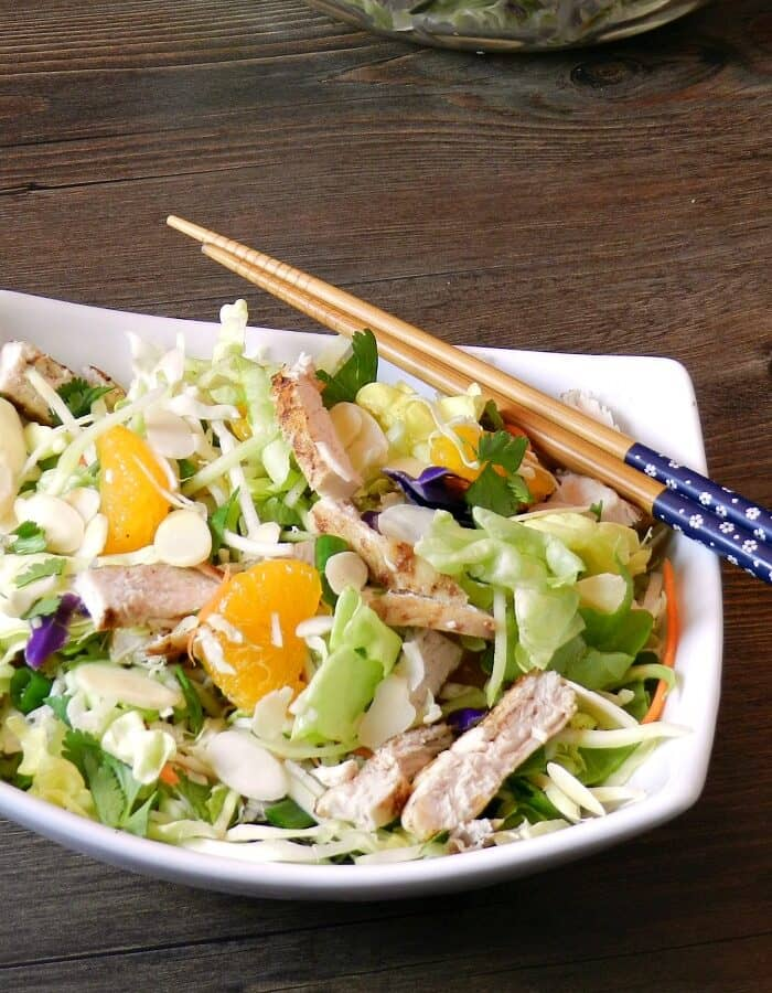 Asian Chicken Salad in a white, rectangle bowl with chop sticks in the upper right hand corner