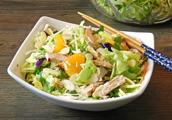 Asian Chicken Salad in a rectangle white bowl with chop sticks laying across the corner