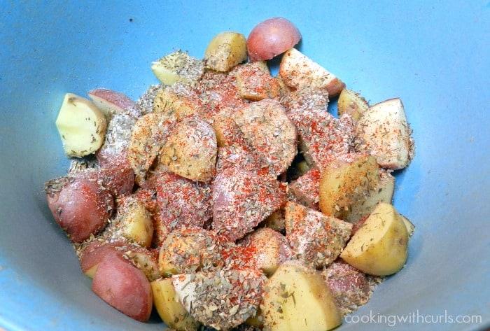 Cut potatoes with seasonings in a blue bowl.