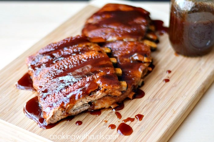 barbecue ribs on a wooden cutting board with a jar of sauce on the side