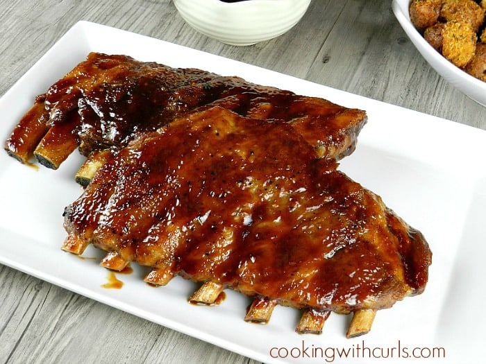 barbecue ribs on a white platter with barbecue sauce and a bowl of potatoes in the background