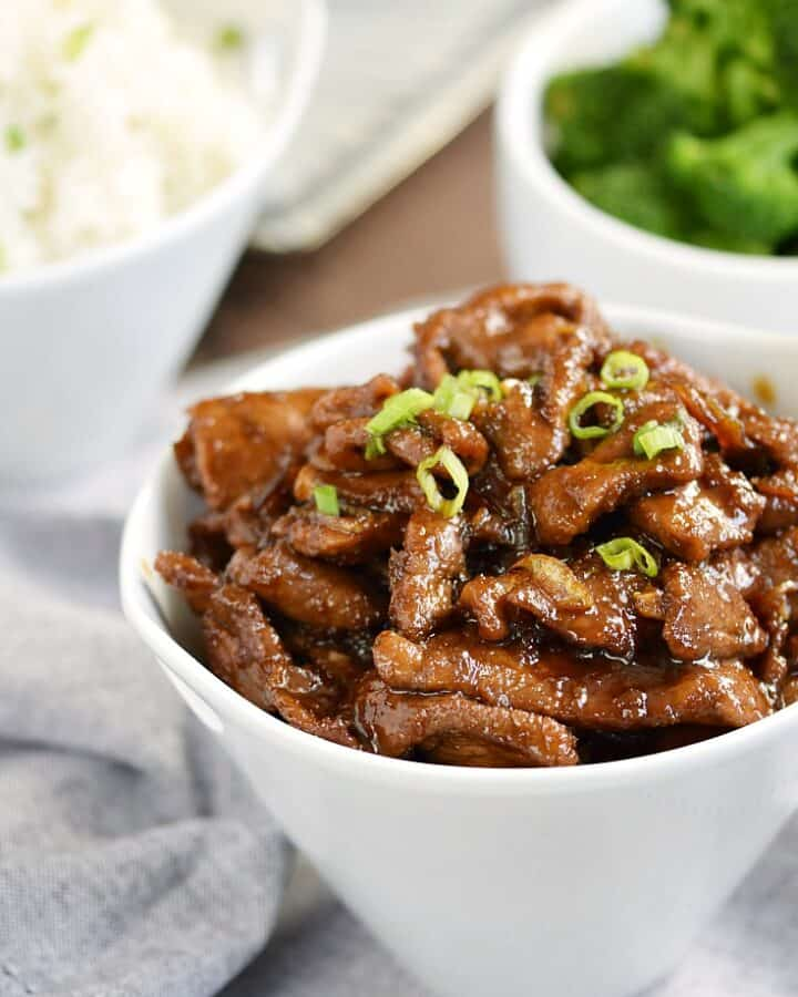 Mongolian Beef with thinly sliced sirloin, tangy Asian sauce, and sweet caramelized onions in a white bowl with rice and broccoli in the background