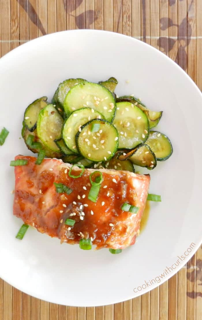 teriyaki sauce covered salmon on a white plate with sauteed zucchini rounds