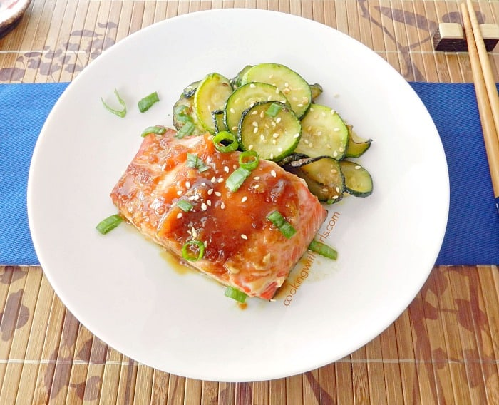 teriyaki glazed salmon on a large with plate with a side of sauteed zucchini slices