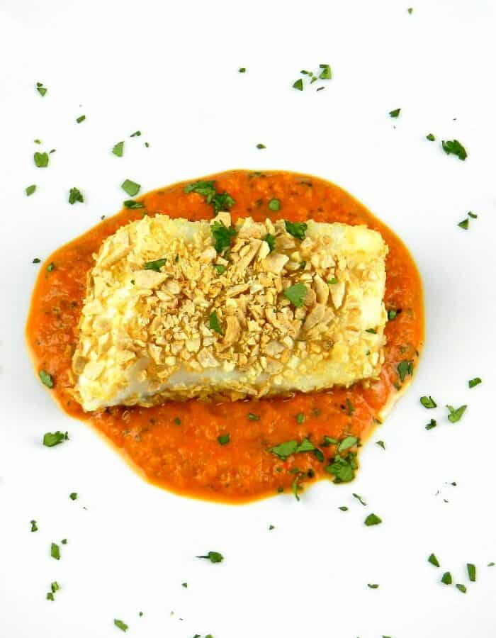 large white plate with roasted red pepper puree in the center with tortilla crusted sea bass laying on top and cilantro sprinkled over the entire plate