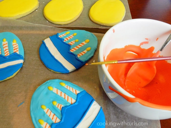 Use a fine paint brush to draw on your royal icing details cookingwithcurls.com