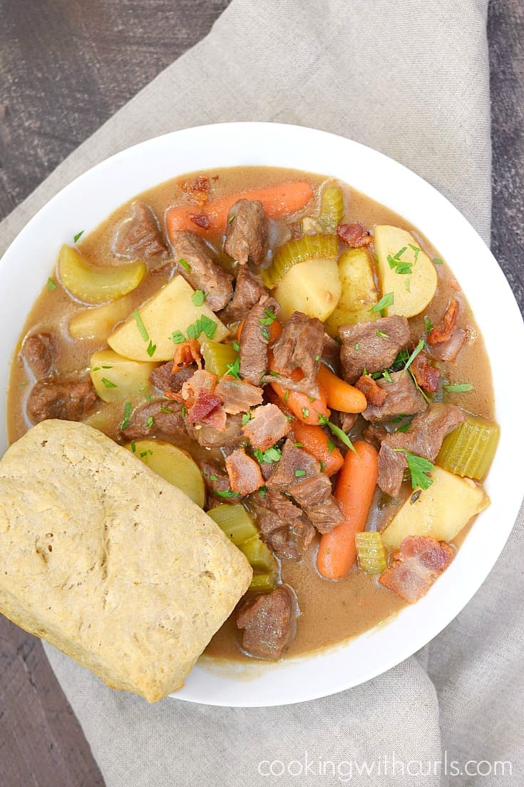 A shot from above of a big white bowl of Beef Stew with Guinness Biscuits sitting on a beige napkin