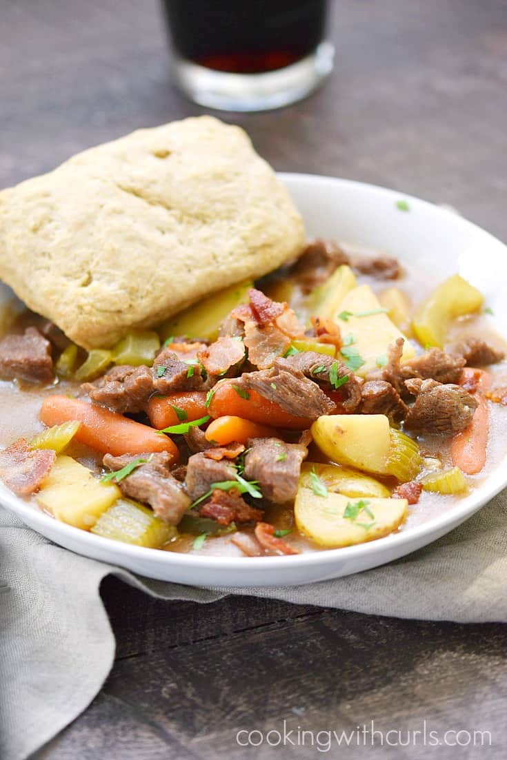 Beef Stew with Guinness Biscuits in a white bowl with a glass of Guinness in the background