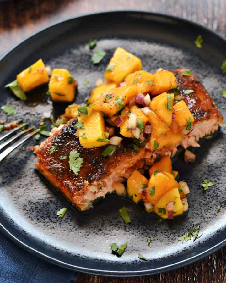 A portion of spice rubbed salmon topped with chopped papaya and mango salsa on a blue plate.