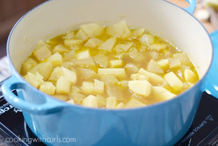 Cooked potato and parsnip chunks in broth inside a blue pot.