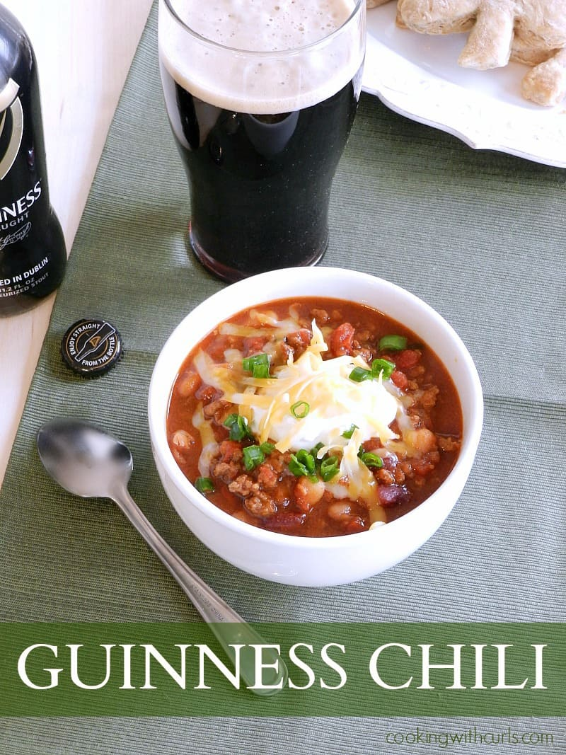 a white bowl full of chili topped with sour cream and green onions with a full glass and an empty bottle of Guinness in the background
