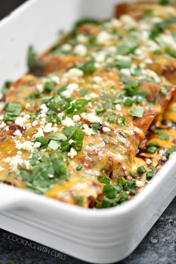 Melted cheese surrounding corn tortillas filled with chicken and red sauce with even more cheese make these Chicken Enchiladas irresistible!! cookingwithcurls.com