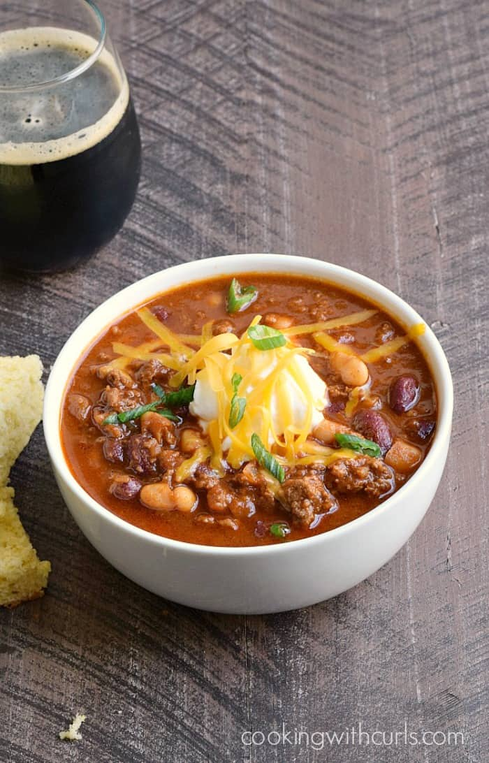 a white bowl of chili topped with sour cream and diced green onions with cornbread and a glass of Guinness on the side