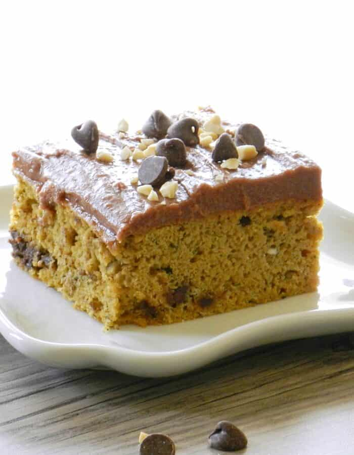 a slice of banana chocolate chip cake with chocolate peanut butter frosting topped with chocolate chips and chopped peanuts sitting on a square white plate