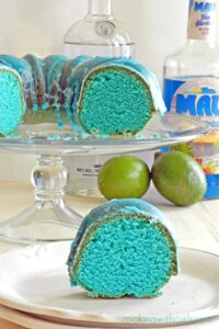 a slice of blue cake on a white plate with the remaining blue bundt cake on a glass cake stand with a bottle of vodka and bottle of blue Curacao in the background