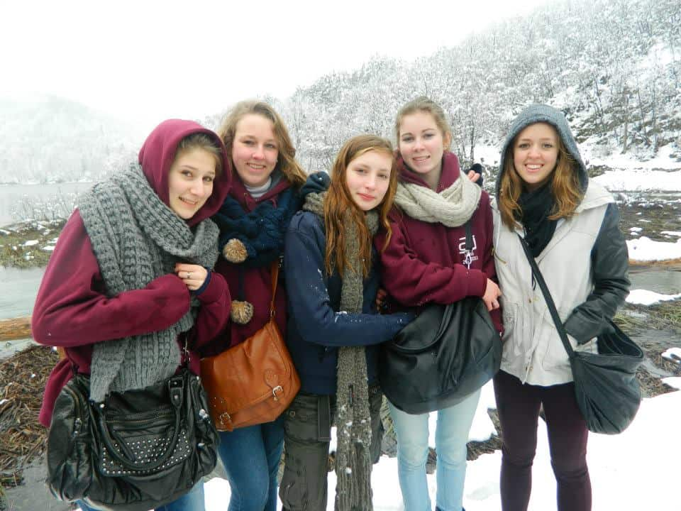 five girls bundled up in winter coats taking a photo in snowy Croatia