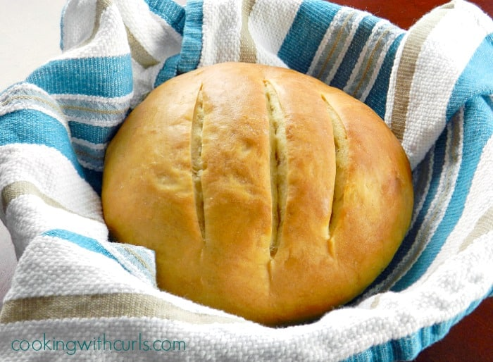 a round loaf of sourdough bread in a towel covered serving bowl