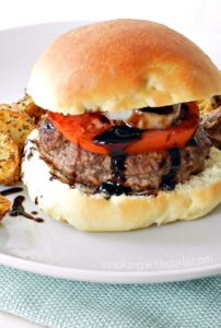 Ground lamb topped with balsamic glaze, onion and tomato surrounded by a hamburger bun sitting on a white plate with a light teal napkin underneath