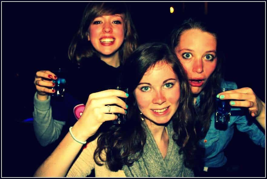 three girls smiling while holding blue kamikaze shots