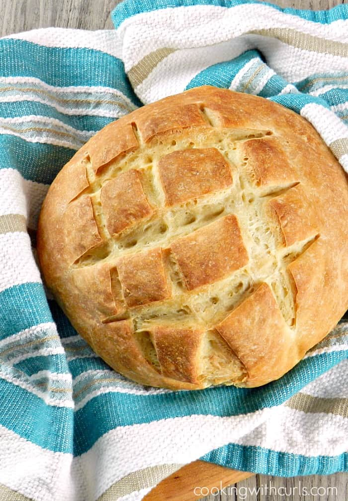 a loaf of sourdough bread with squares cut into the top surrounded by a teal and white striped dish towel