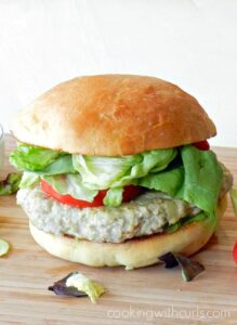 ground chicken burger topped with lettuce and tomato with a fluffy hamburger bun sitting on a wooden cutting board