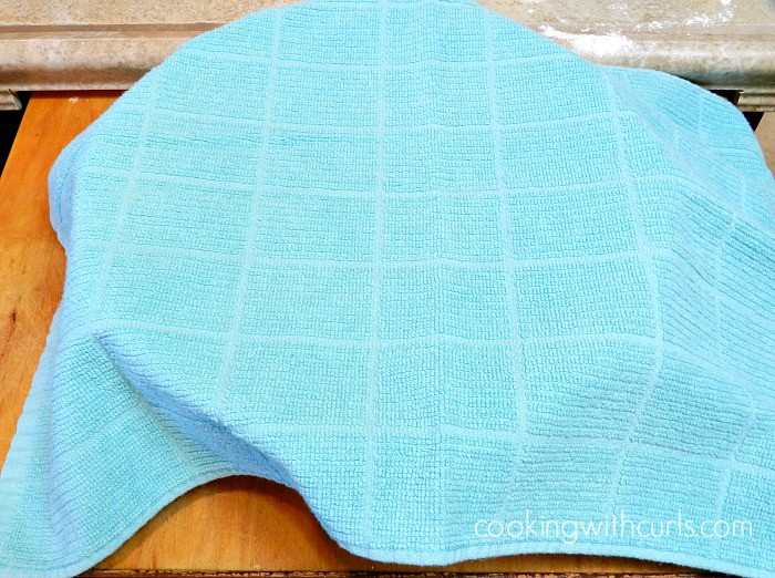 a teal towel draped over a large bowl to allow the dough to rise