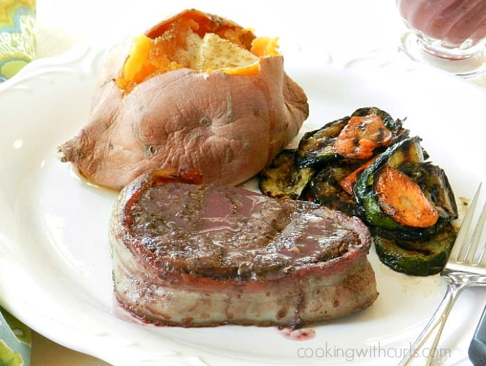 Bacon Wrapped Filet Mignon with Red Wine Sauce, sweet potato and grilled vegetables on a white plate