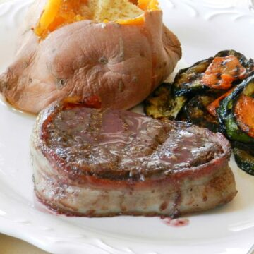 Bacon Wrapped Filet Mignon with Red Wine Sauce, grilled vegetables and a sweet potato on a white plate