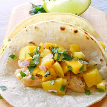 Baked Fish Tacos topped with Papaya Mango Salsa sitting on a wood cutting board