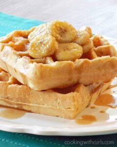 two waffles on a white plate topped with caramelized bananas