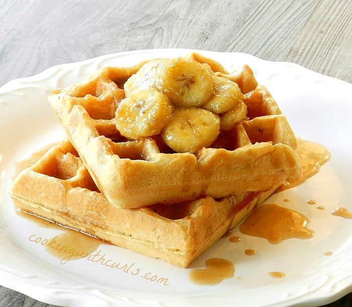 bananas foster belgian waffles on a white plate
